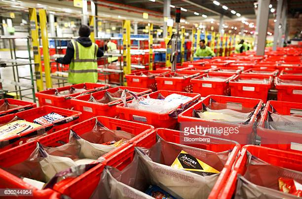 Employees load completed customer order crates onto trolleys at the Ocado Group Plc distribution centre in Dordon UK on Friday Dec 16 2016 Ocado...