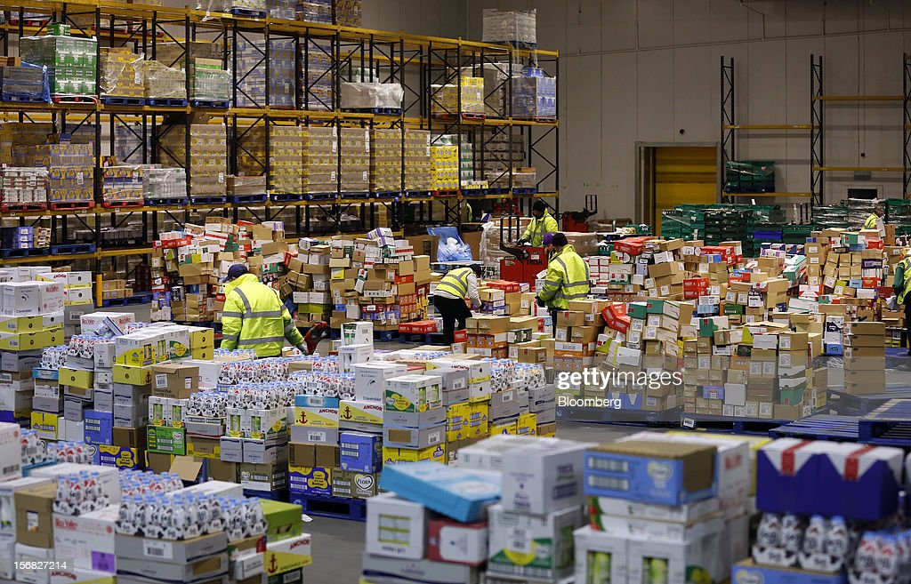 Employees load pallets with produce ahead of transporting to stores inside WM Morrison Supermarkets Plc's distribution center in Wakefield, U.K., on Thursday, Nov. 22, 2012. Britain's economy will return to growth next year after stagnating in 2012, with expansion weighted in the second half, according to Bank of England projections published yesterday. Photographer: Simon Dawson/Bloomberg via Getty Images