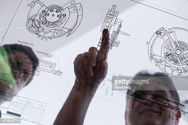Employees look at a wristwatch mechanism design document at Moritz Grossmann GmbH luxury watchmakers in Glasshuette Germany on Wednesday May 27 2015...