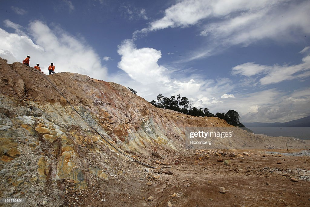 Employees look out towards the open pit of the G-Resources Group Ltd. Martabe gold and silver mine in Batang Toru, North Sumatra province, Indonesia, on Tuesday, Feb. 12, 2013. G-Resources is scheduled to announce financial results on Feb. 28. Photographer: Dadang Tri/Bloomberg via Getty Images