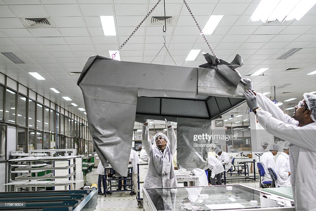 Employees lower a hood onto an inspection chamber work bench on the solar photovoltaic module production line at the Tata Power Solar Systems Ltd. manufacturing plant in Bangalore, India, on Tuesday, June 11, 2013. Tata Groups solar unit is expanding its business building plants for customers, forecasting that offices and factories will be paying more for grid power than solar by 2016 in most Indian states. Photographer: Dhiraj Singh/Bloomberg via Getty Images