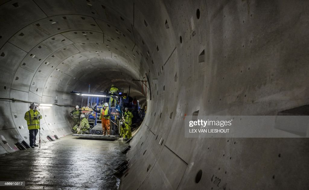 Employees make a flat bottom in the round tunnels of the North/South subway line with a pavermachine in Amsterdam, on February 5,2014. Concrete will be poured in three different phases, on which the metro rail can be installed later. AFP PHOTO /ANP / LEX VAN LIESHOUT - Netherlands out - Belgium out -