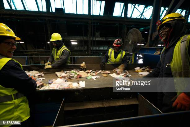 Employees manually sort out as a conveyer belts transport sorted and unsorted materials during the recyclables recovery process at the Materials...