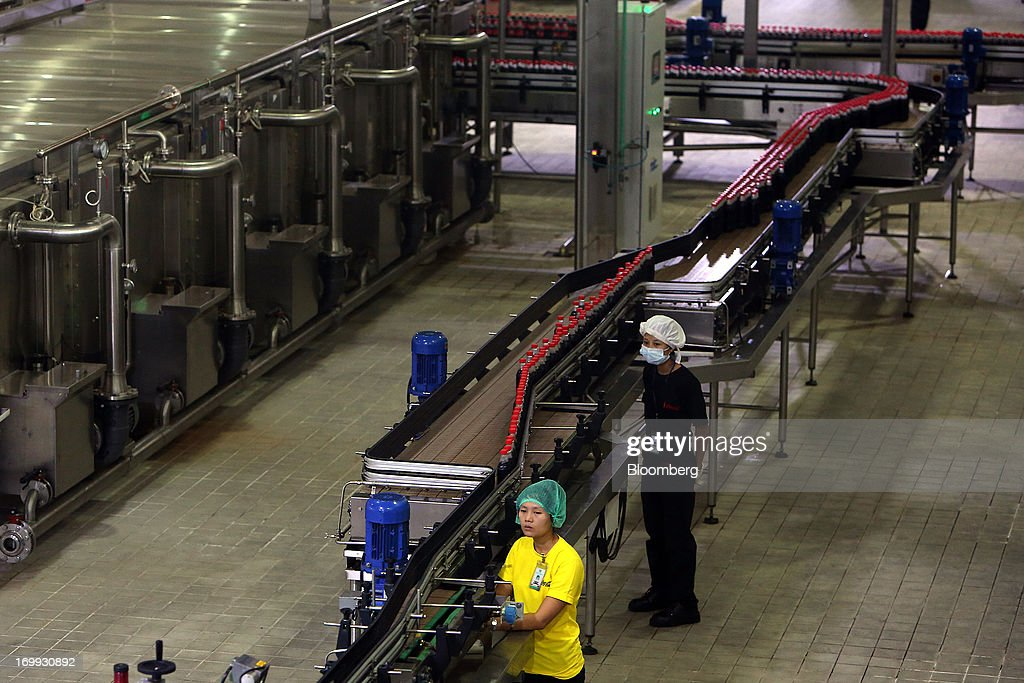 Employees monitor operations as bottles of Coca-Cola soda move along the production line at the Coca-Cola Co. bottling plant in Hmawbi, Myanmar, on Tuesday, June 4, 2013. Coca-Cola Co. Chief Executive Officer Muhtar Kent marked the return of the world's largest soda maker to Myanmar after 60 years by opening a bottling plant and pledging more investment in the newly opened economy. Photographer: Dario Pignatelli/Bloomberg via Getty Images