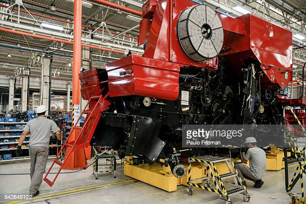 Employees mount a grain combine At CASE Combines assembly line Sorocaba Brazil on Wednesday September 18th 2013