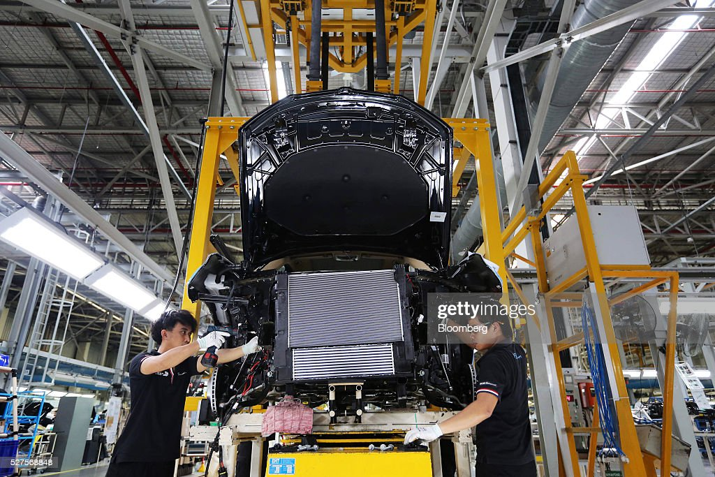 Employees mount an engine onto a BMW AG X3 vehicle at a BMW manufacturing plant in Pluak Daeng, Rayong Province, Thailand, on Tuesday, May 3, 2016. BMW's profit declined 2.5 percent in the first quarter on investment in new technologies like self-driving cars to defend its status as the world's biggest maker of luxury vehicles. Photographer: Dario Pignatelli/Bloomberg via Getty Images