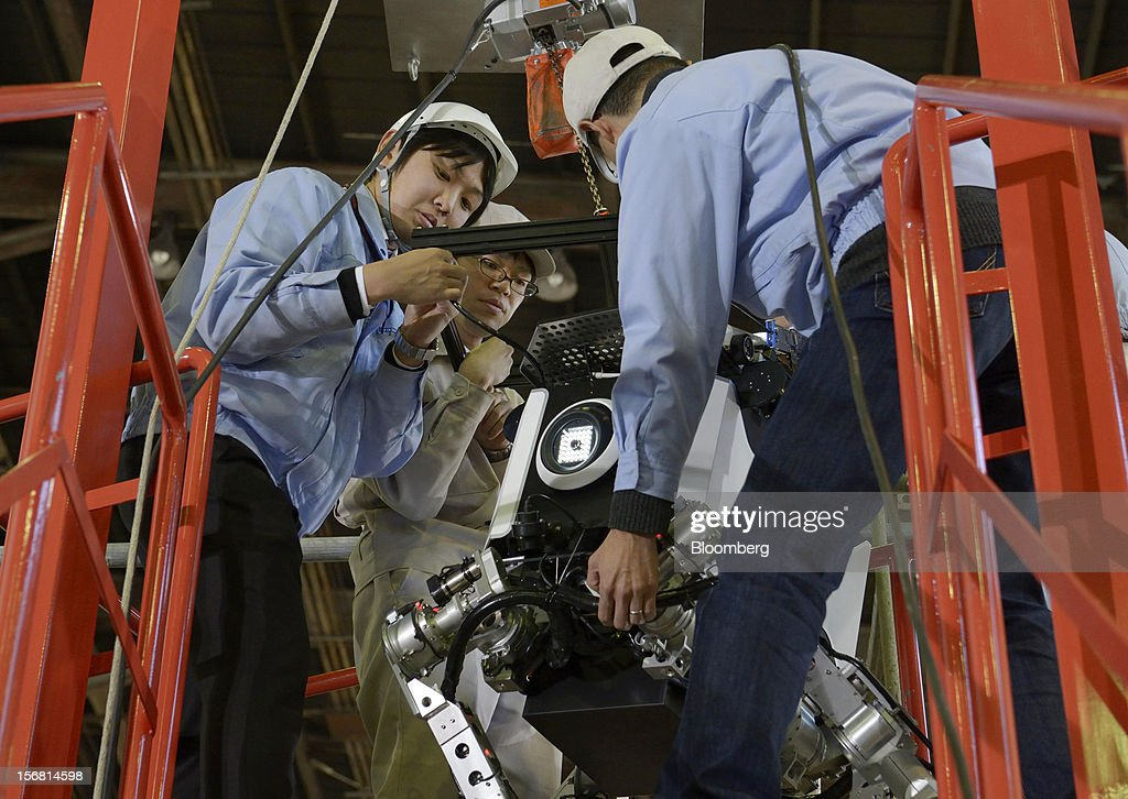 Employees move a Toshiba Corp. tetrapod robot during a demonstration at the company's Yokohama Complex in Yokohama City, Kanagawa Prefecture, Japan, on Wednesday, Nov. 21, 2012. Toshiba's new robot was developed to work in areas too dangerous for humans. Photographer: Akio Kon/Bloomberg via Getty Images