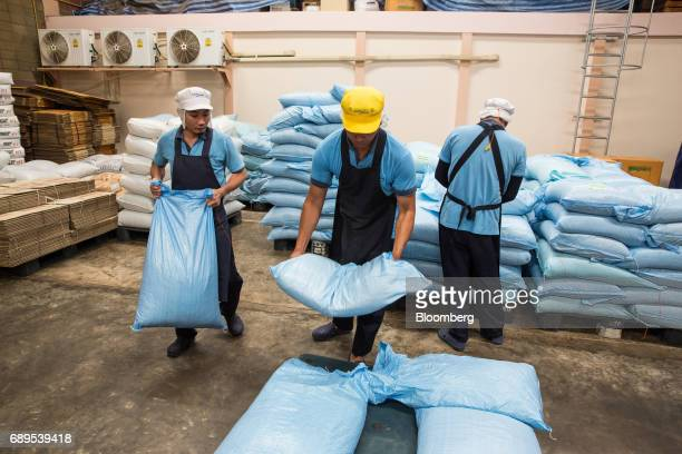 Employees move bags of garlic in a warehouse at the Nithi Foods Co factory in the San Pa Tong district of Chiang Mai Thailand on Tuesday May 23 2017...