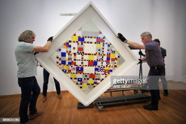 Employees move the painting 'Victory Boogie Woogie' by Dutch painter Pieter Cornelis Mondriaan aka Piet Mondrian in the Municipal Museum in The Hague...