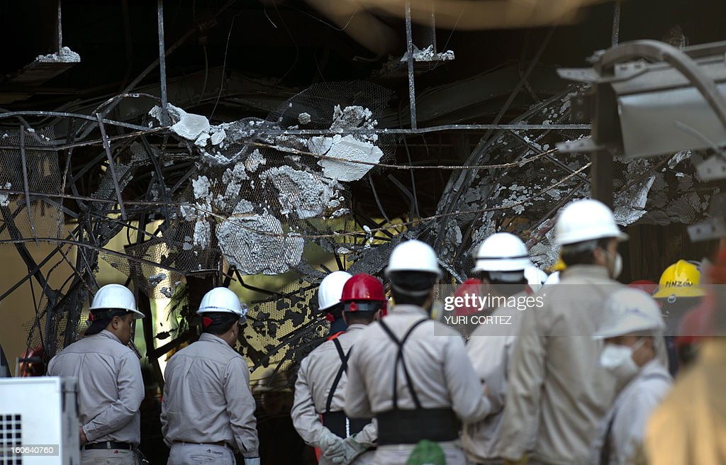 PEMEX employees observe damages at the building of state-owned Mexican oil giant Pemex, in Mexico City on February 4, 2013. An explosion rocked last week the skyscraper, leaving up to 36 dead and 121 injured. CORTEZ