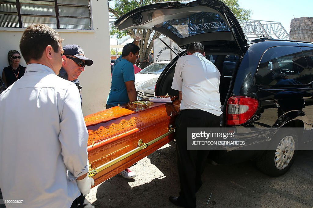Employees of a funeral parlor carry a coffin in Santa Maria, 550 Km from Porto Alegre, southern Brazil on January 28, 2013, where more than 230 people died and 116 more were injured. Shocked survivors, mostly science students in Santa Maria, described how scores of revelers were trampled to death or succumbed to smoke inhalation as blocked exits and rising flames caused panic AFP PHOTO / Jefferson BERNARDES