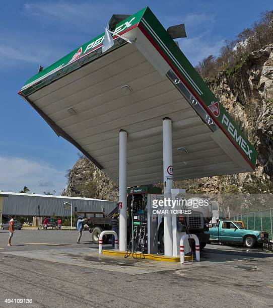 Employees of a PEMEX petrol station work to fix the roof of one of the pumps after the passage of hurricane Patricia in Melaque Jalisco state Mexico...