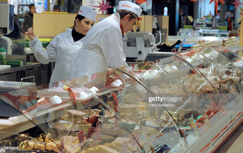 Employees of a supermarket Auchan works at a cooked pork meats stand on December 27, 2012 in Saint-Sebastien-sur-Loire, western France.