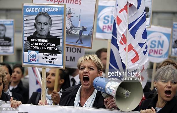 Employees of Air France shout slogans and hold placard reading 'Gagey get away' during a demonstration in front of the company headquarters during...