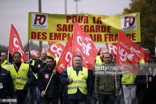 Employees of Air France wave CGT union flags as they take part in a demonstration in front of the company headquarters during the launch of the plan...