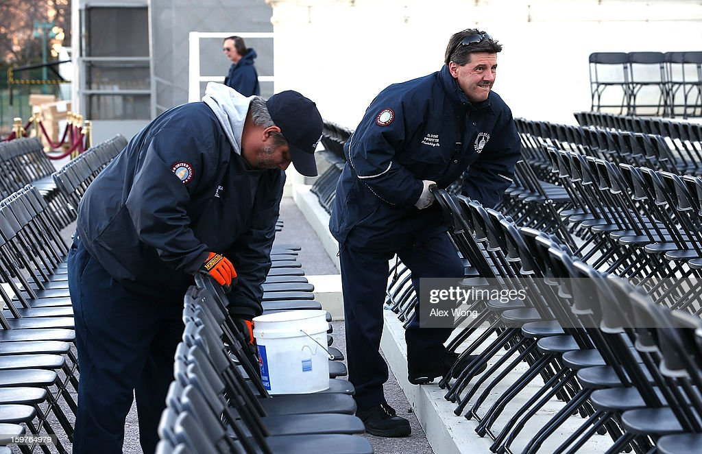 Employees of Architect of the Capitol Robert Petruska (L) and David Dove help to line-up chairs for the presidential inauguration at the West Front of the U.S. Capitol January 20, 2013 in Washington, DC. President Barack Obama will be officially sworn in for his second term today during a short private ceremony at the Blue Room of the White House. A full public ceremony will be held at the West Front of the Capitol on Monday.