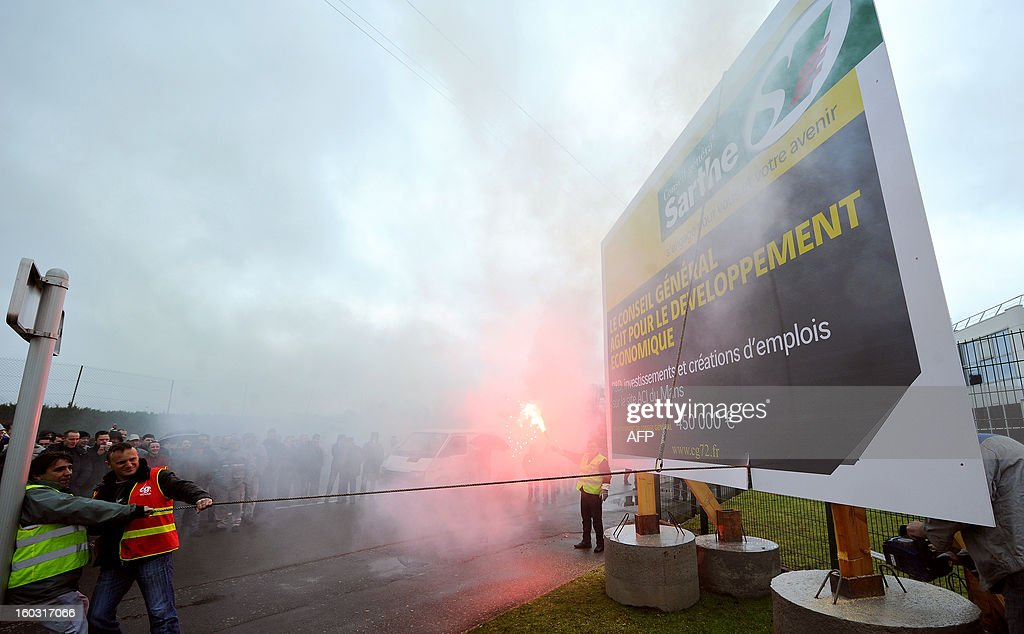 Employees of Auto Chassis International, owned by French automaker Renault, protest against job cuts on January 29, 2013 in Le Mans, western France. Workers dismanteled a giant panel of the General Council of the Sarthe department reading 'Here The General Council work on economic development, investments and job creations. Investments 450,000 €'. Renault, which announced last week plans to cut 7,500 jobs in France through natural attrition and early retirement, has pledged not to close any factories if unions agree to changes that allow the company to compete more effectively worldwide.