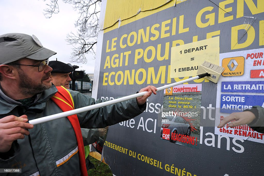 Employees of Auto Chassis International, owned by French automaker Renault, protest against job cuts set stickers on an advertising boad on January 29, 2013 in Le Mans, western France, as they protest as part of a nationwide action day. Workers dismanteled a giant panel of the General Council of the Sarthe department reading 'Here The General Council work on economic development, investments and job creations. Investments 450,000 €'. Renault, which announced last week plans to cut 7,500 jobs in France through natural attrition and early retirement, has pledged not to close any factories if unions agree to changes that allow the company to compete more effectively worldwide.