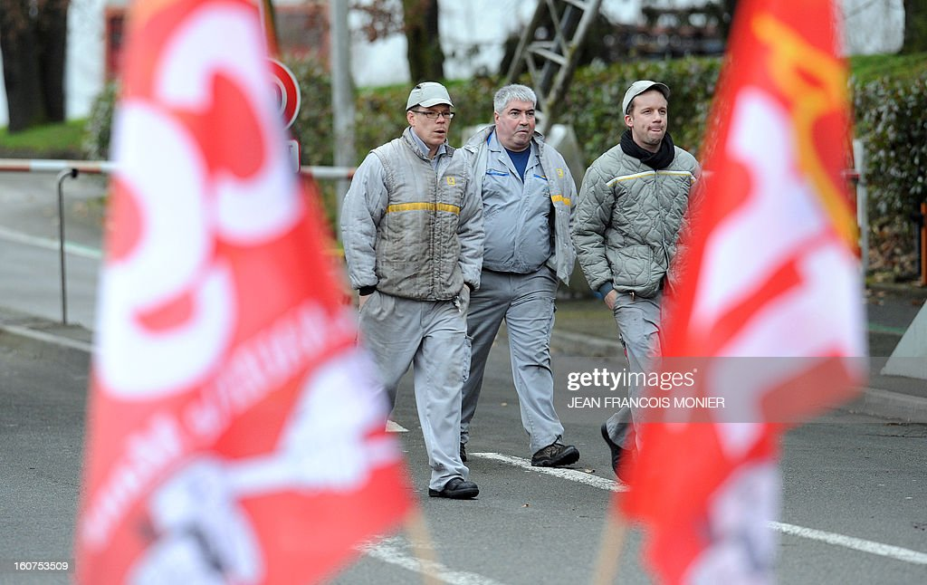 Employees of Auto Chassis International, owned by French automaker Renault,walk next to flags of French union CGT during a protest against job cuts on February 5, 2013 in Le Mans, western France. Renault, which announced plans to cut 7,500 jobs in France through natural attrition and early retirement has pledged not to close any factories if unions agree to changes that allow the company to compete.