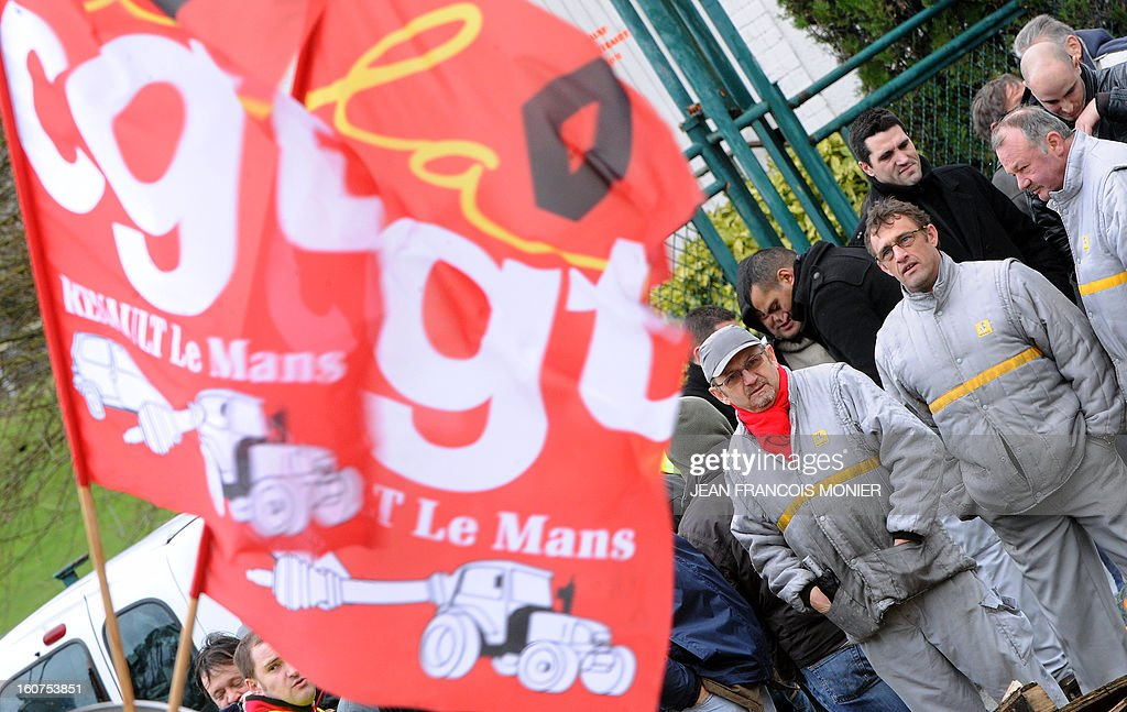 Employees of Auto Chassis International, owned by French automaker Renault, stand next to flags of French union CGT during a protest against job cuts on February 5, 2013 in Le Mans, western France. Renault, which announced plans to cut 7,500 jobs in France through natural attrition and early retirement has pledged not to close any factories if unions agree to changes that allow the company to compete.