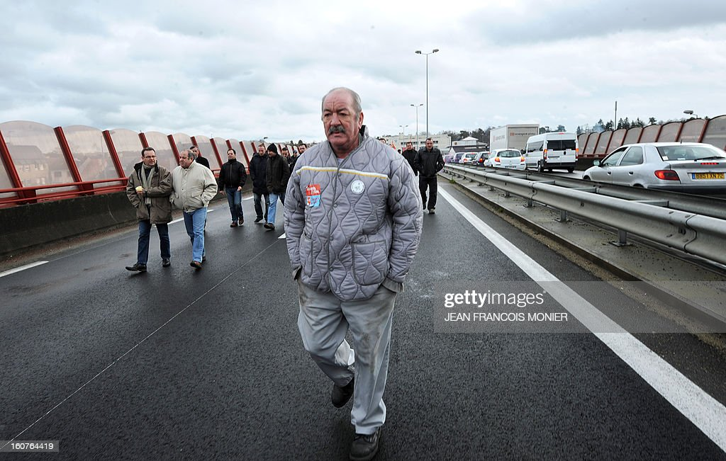 Employees of Auto Chassis International, owned by French automaker Renault, demonstrate on the Le Mans' bypass to protest against job cuts on February 5, 2013 in Le Mans, western France. Renault, which announced plans to cut 7,500 jobs in France through natural attrition and early retirement has pledged not to close any factories if unions agree to changes that allow the company to compete. Renault officials gave the document to union leaders at a meeting, which said if there was no deal was made on measures to boost the company's competitive position 'the promise not to close factories could not be kept and closures would occur. AFP PHOTO / JEAN-FRANCOIS MONIER