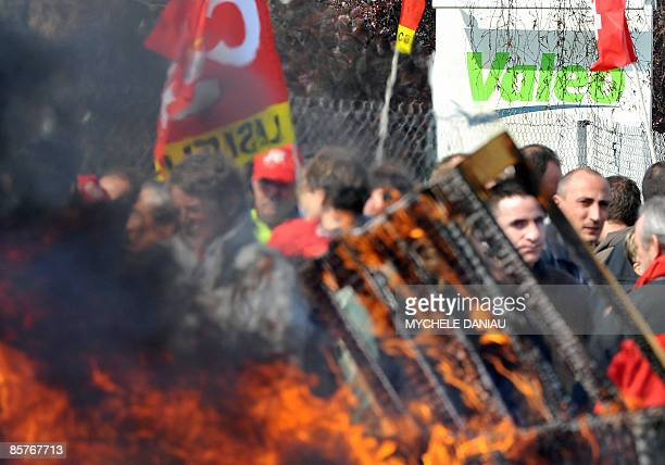 Employees of auto parts supplier Valeo block the entrance of the factory with burning pallets in Mondeville western France on April 2 2009 In...