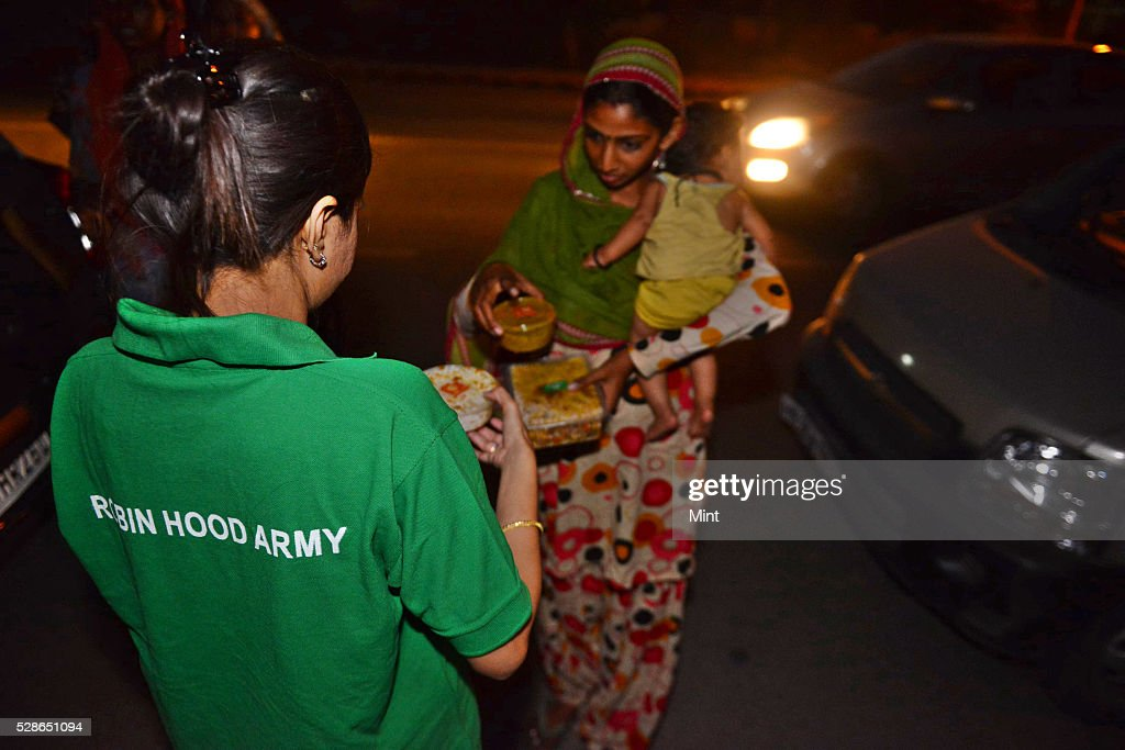 Employees of Bite Club, an online aggregator of home-cooked food run by Ecstasy E-Ordering Pvt. Ltd distributing food in slum in collaboration with volunteers of Robin Hood Army on October 4, 2015 in New Delhi, India.