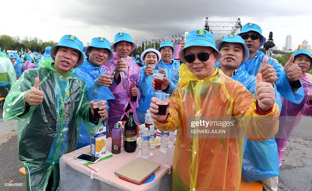 Employees of Chinese company Tiens pose as they drink 'sangria' during a reception in Madrid on May 6, 2016. Some 2,500 employees of Chinese conglomerate Tiens arrived in Spain on May 4, 2016 for an all-paid holiday treat complete with a giant paella and sangria party, in a trip costing a grand total of seven million euros ($8 million) hailed as helping the ailing local economy. . JULIEN