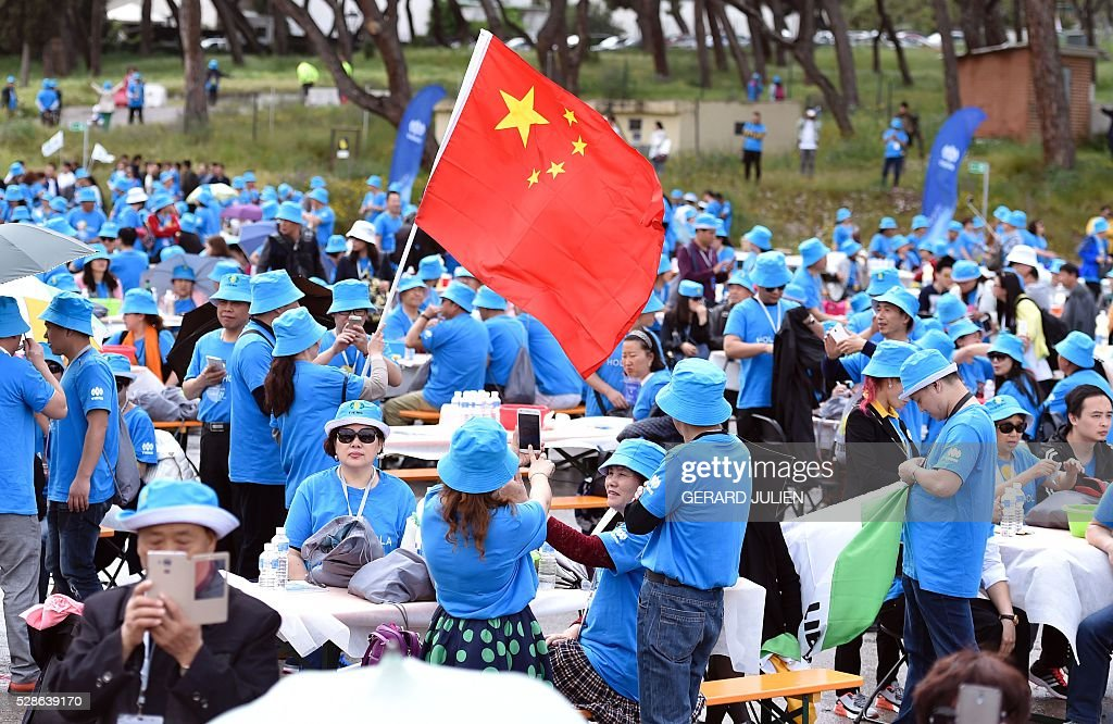 Employees of Chinese company Tiens wave a chinese flag as they take part in a reception in Madrid on May 6, 2016. Some 2,500 employees of Chinese conglomerate Tiens arrived in Spain on May 4, 2016 for an all-paid holiday treat complete with a giant paella and sangria party, in a trip costing a grand total of seven million euros ($8 million) hailed as helping the ailing local economy. . JULIEN