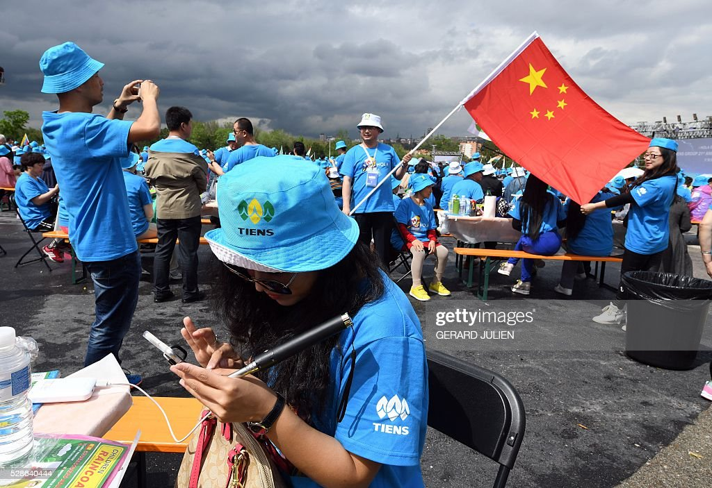 Employees of Chinese company Tiens wave a Chinese flag during a reception in Madrid on May 6, 2016. Some 2,500 employees of Chinese conglomerate Tiens arrived in Spain on May 4, 2016 for an all-paid holiday treat complete with a giant paella and sangria party, in a trip costing a grand total of seven million euros ($8 million) hailed as helping the ailing local economy. . JULIEN