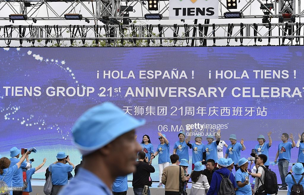 Employees of Chinese company Tiens wave on a stage as they take part in a reception in Madrid on May 6, 2016. Some 2,500 employees of Chinese conglomerate Tiens arrived in Spain on May 4, 2016 for an all-paid holiday treat complete with a giant paella and sangria party, in a trip costing a grand total of seven million euros ($8 million) hailed as helping the ailing local economy. . JULIEN