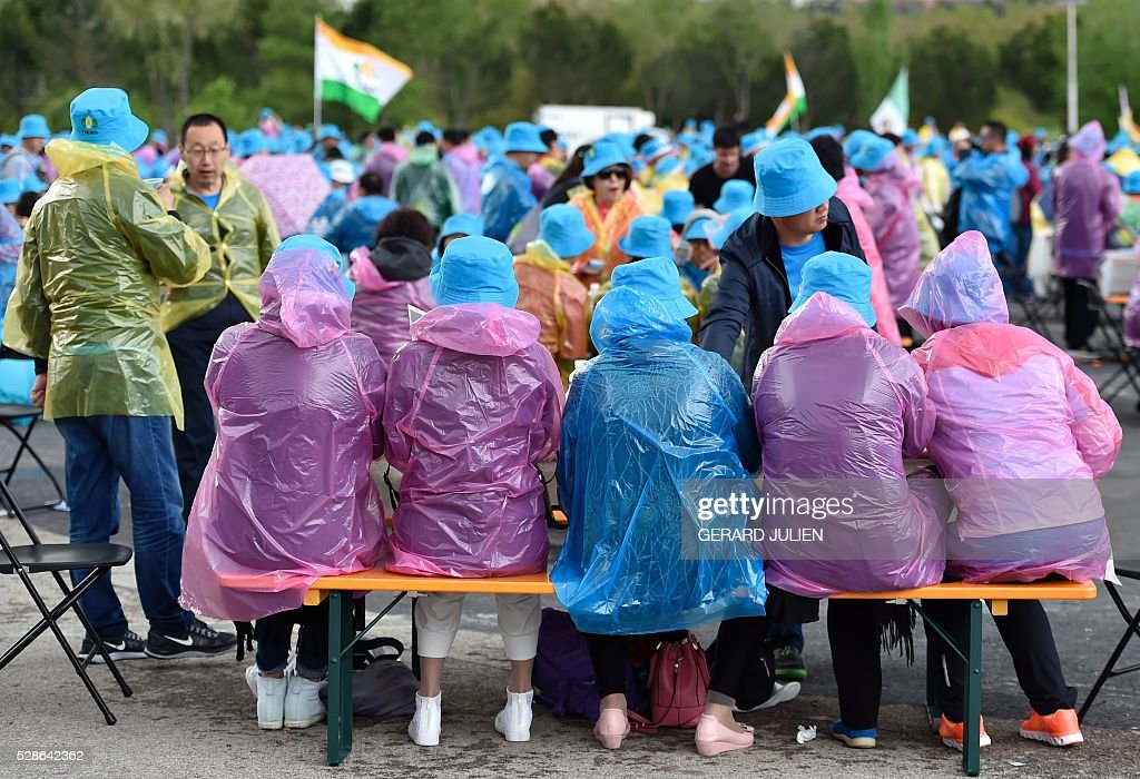 Employees of Chinese company Tiens wear raincoats as they take part in a reception in Madrid on May 6, 2016. Some 2,500 employees of Chinese conglomerate Tiens arrived in Spain on May 4, 2016 for an all-paid holiday treat complete with a giant paella and sangria party, in a trip costing a grand total of seven million euros ($8 million) hailed as helping the ailing local economy. . JULIEN