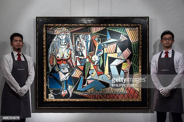 Employees of Christie's auction house stand by the Picasso painting titled 'Les Femmes d'Algers' in Hong Kong on April 1 2015 The painting was shown...