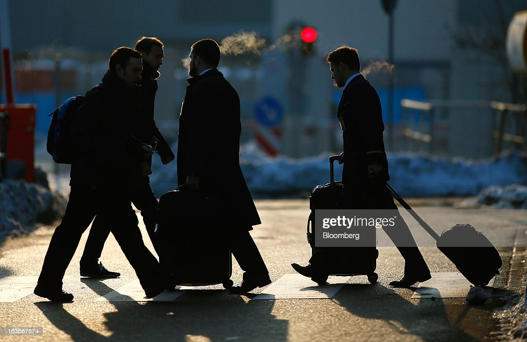 Employees of Deutsche Lufthansa AG cross a pedestrian crossing at Frankfurt airport in Frankfurt, Germany, on Thursday, March 14, 2013. Deutsche Lufthansa AG agreed to renew its short-haul fleet with 100 mostly fuel-efficient jets from Airbus SAS, as the airline seeks to cut kerosene costs that constitute its single biggest expense. Photographer: Ralph Orlowski/Bloomberg via Getty Images