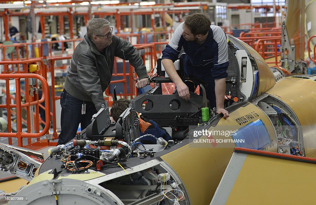 Employees of EADS company Cassidian assemble an Eurofighter plane for the German Air Force at the Cassidian production line in Manching, southern Germany, on February 28, 2013.