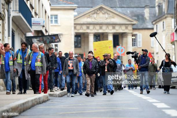 Employees of French auto parts manufacturer GMS arrive at the trade court of Poitiers central France on September 4 before a hearing on a takeover of...