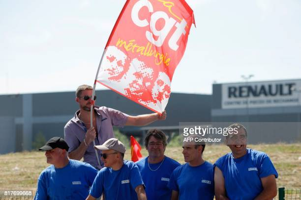 Employees of French auto parts manufacturer GMS threatened with liquidation hold a flag of French union CGT as they block a site of their supplier...