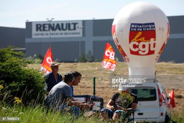 Employees of French auto parts manufacturer GMS threatened with liquidation sit next to flags of French union CGT as they block a site of their...