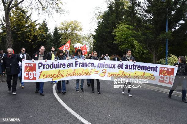 Employees of French carmaker PSA Peugeot Citroen hold a banner during a demonstration organised by the CGT Union to call to preserve jobs and ask for...