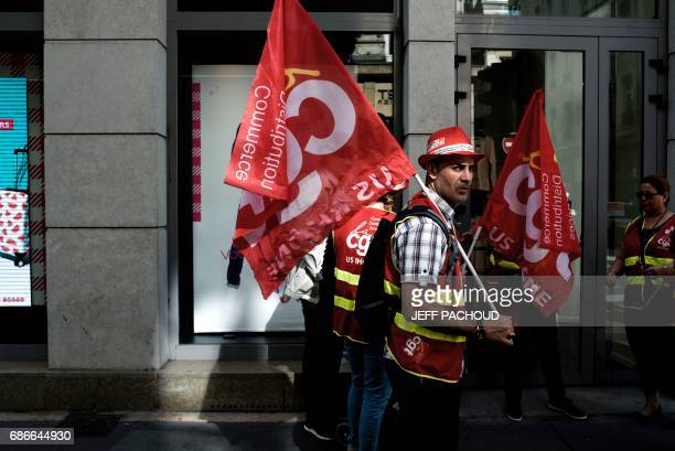 Employees of French department store Tati carry flags during a demonstration in front of a Tati store on May 22 2017 in Lyon Five companies submitted...