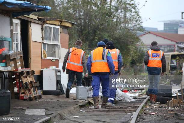 Employees of French stateowned railway company SNCF walk in a camp where some 800 people of the Roma community were living following its evacuation...
