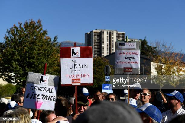 Employees of General Electric HydroAlstom hold up placards during a visit of La France Insoumise leftist party's leader and parliamentary group...