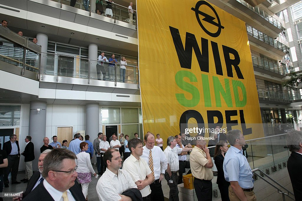 Employees of German car maker Adam Opel GmbH, a subsidiary company of U.S. carmaker General Motors, stand in front of a a huge poster at the headquarters during a news conference on June 3, 2009 in Ruesselsheim near Frankfurt am Main, Germany. After tough negotiations Canadian car-parts maker Magna International Inc. was chosen to rescue General Motors European division, including Opel's locations in Kaiserslautern, Eisenach, Bochum and their headquarters in Ruesselsheim with bridge loans, provided by German government.