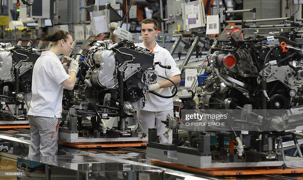 Employees of German car maker Audi work in the engine assembly section of the car factory in Ingolstadt, southern Germany, on March 11, 2013. Audi presents further details on the company results 2012 at the Audi Annual Press Conference on March 12, 2013 in Ingolstadt. AFP PHOTO/CHRISTOF STACHE