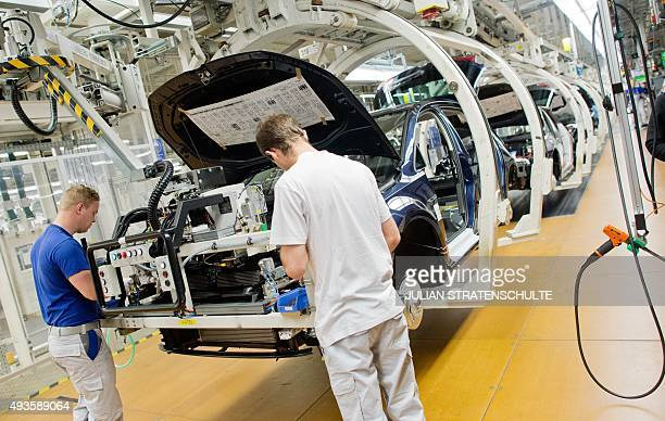 Employees of German car maker Volkswagen work on a Golf VII car at an assembly line at VW plant in Wolfsburg central Germany on October 21 2015...
