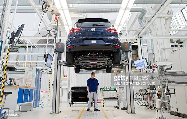 Employees of German car maker Volkswagen work on an electric car eGolf at an assembly line at VW plant in Wolfsburg central Germany on October 21...