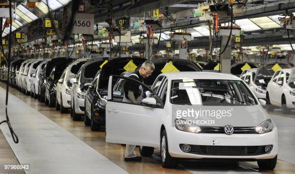 Employees of German car manufacturer Volkswagen check VW Golf cars on March 8 2010 at the main plant in Wolfsburg northern Germany Volkswagen holds...