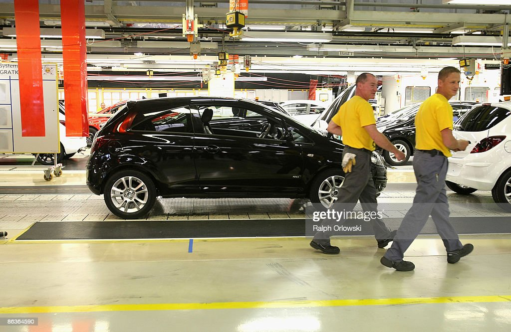 Employees of German carmaker Adam Opel GmbH walk past an Opel Corsa at a plant on May 4, 2009 in Eisenach, Germany. Representatives of the German government, officials of car manufacturer Opel and managers of Italian carmaker Fiat will meet today in Berlin to discuss a merger between Fiat, Opel and U.S. carmaker Chrysler.