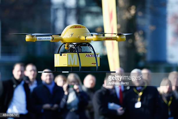 Employees of German postal carrier Deutsche Post and visitors watch as a quadcopter drone arrives with a small delivery at Deutsche Post headquarters...