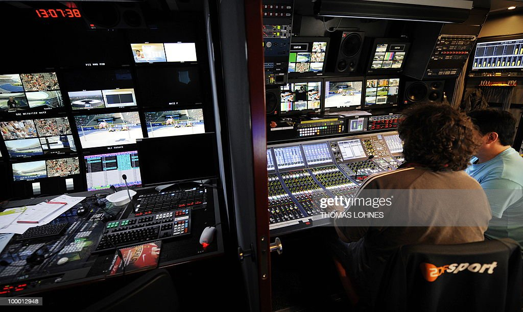 Employees of German television broadcaster ZDF sits at their post in front of monitors in an outside broadcast van at the Olympic Stadium during the 2009 IAAF Athletics World Championships on August 19, 2009 in Berlin.